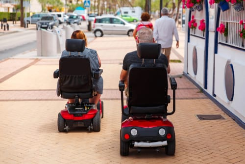 Couple driving mobility scooters