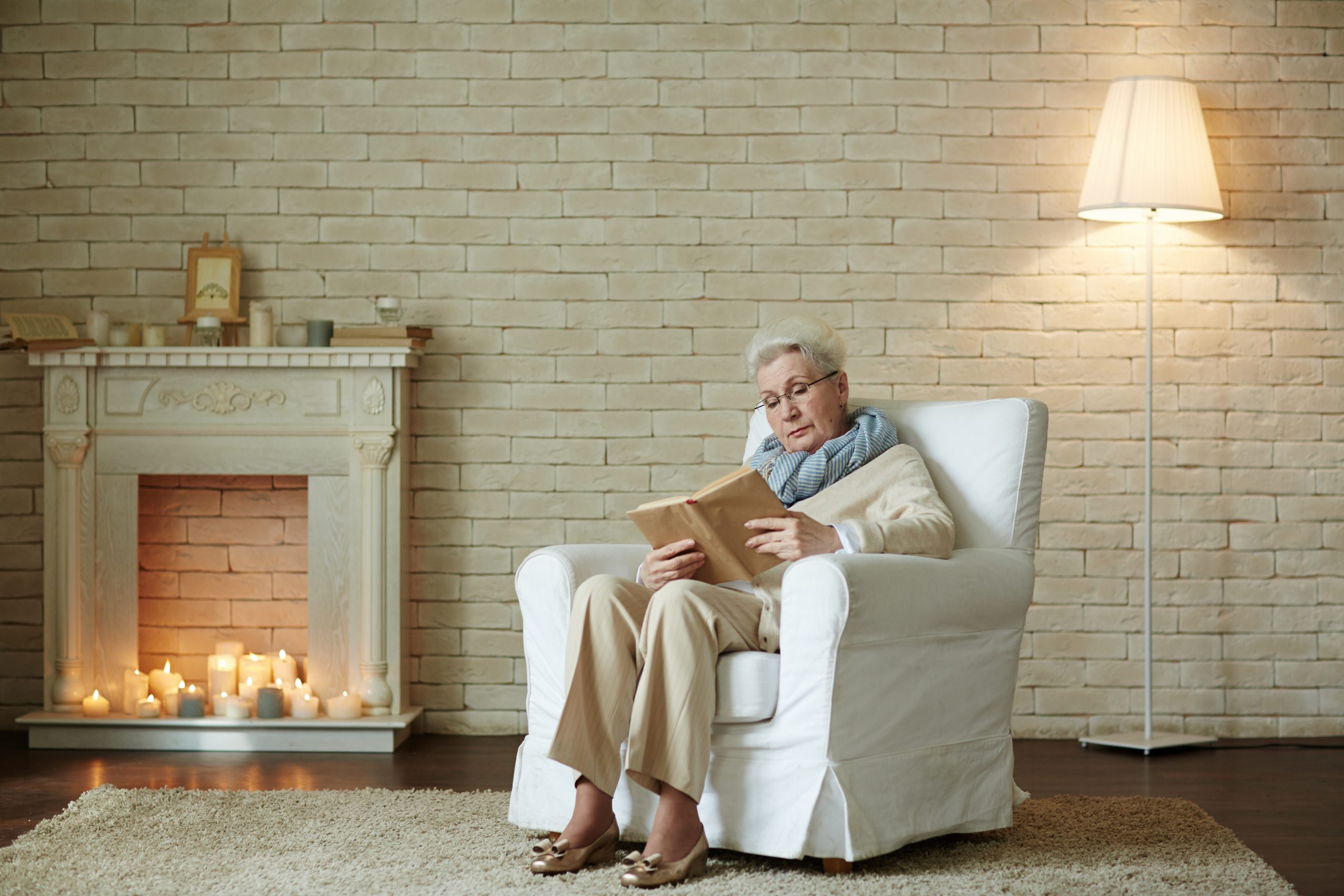 old woman in armchair reading by fire to keep warm in winter