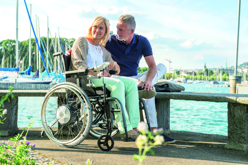 Woman in wheelchair outside near water with man sitting next to her