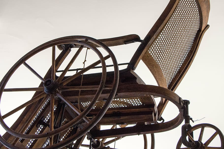 A vintage wheelchair, similar to the first wheelchair in it's material composition.