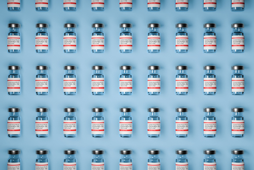 vaccine rollout for COVID shows vials lined up against wall