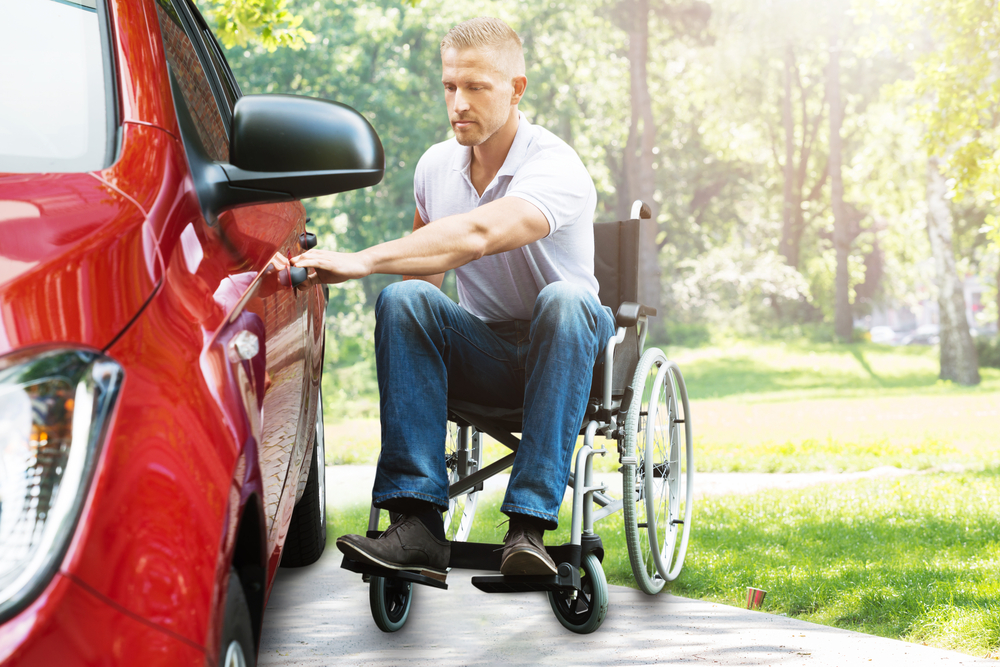 a disability insurance specialist insures this person in wheelchair transferring to car